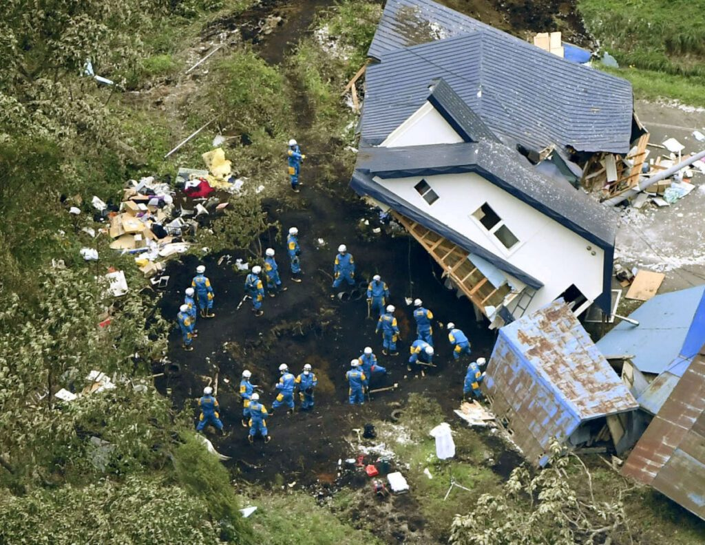 Police officers search for survivors from a house damaged by a landslide caused by an earthquake in atsuma town